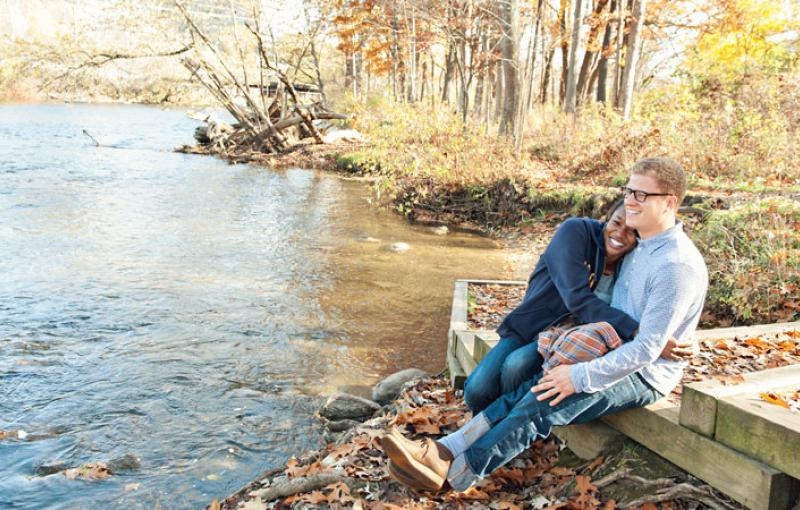 A couple snuggles up next to the Huron River in Ann Arbor during autumn