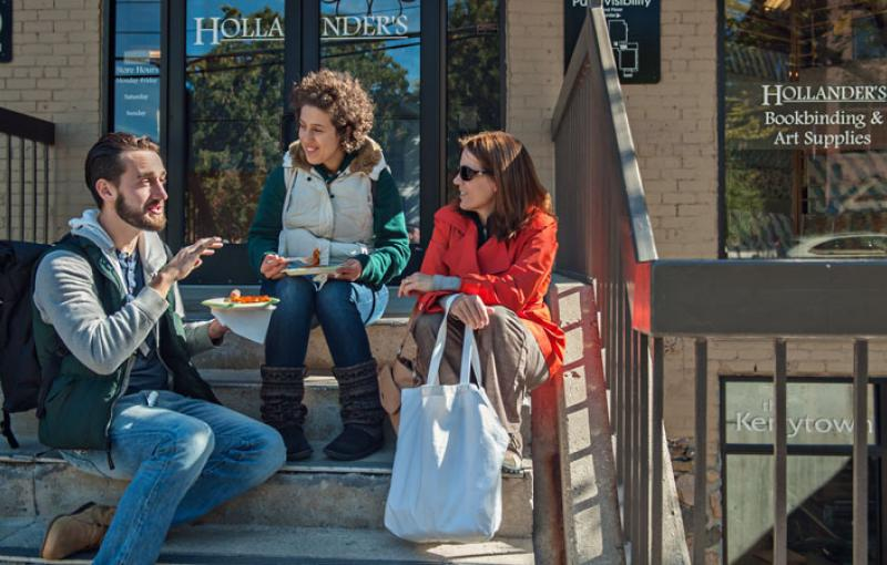 Friends have a meal together on the steps of Kerrytown Shops