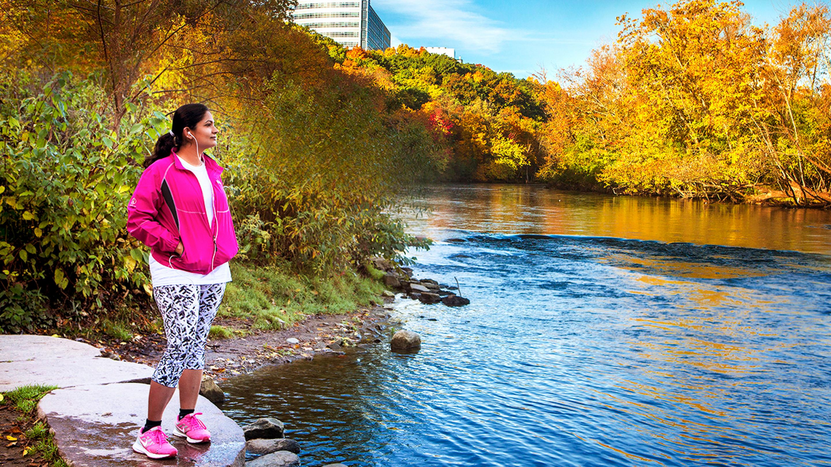 A jogger gazes at the Huron River during autumn in the Ann Arbor Arboretum