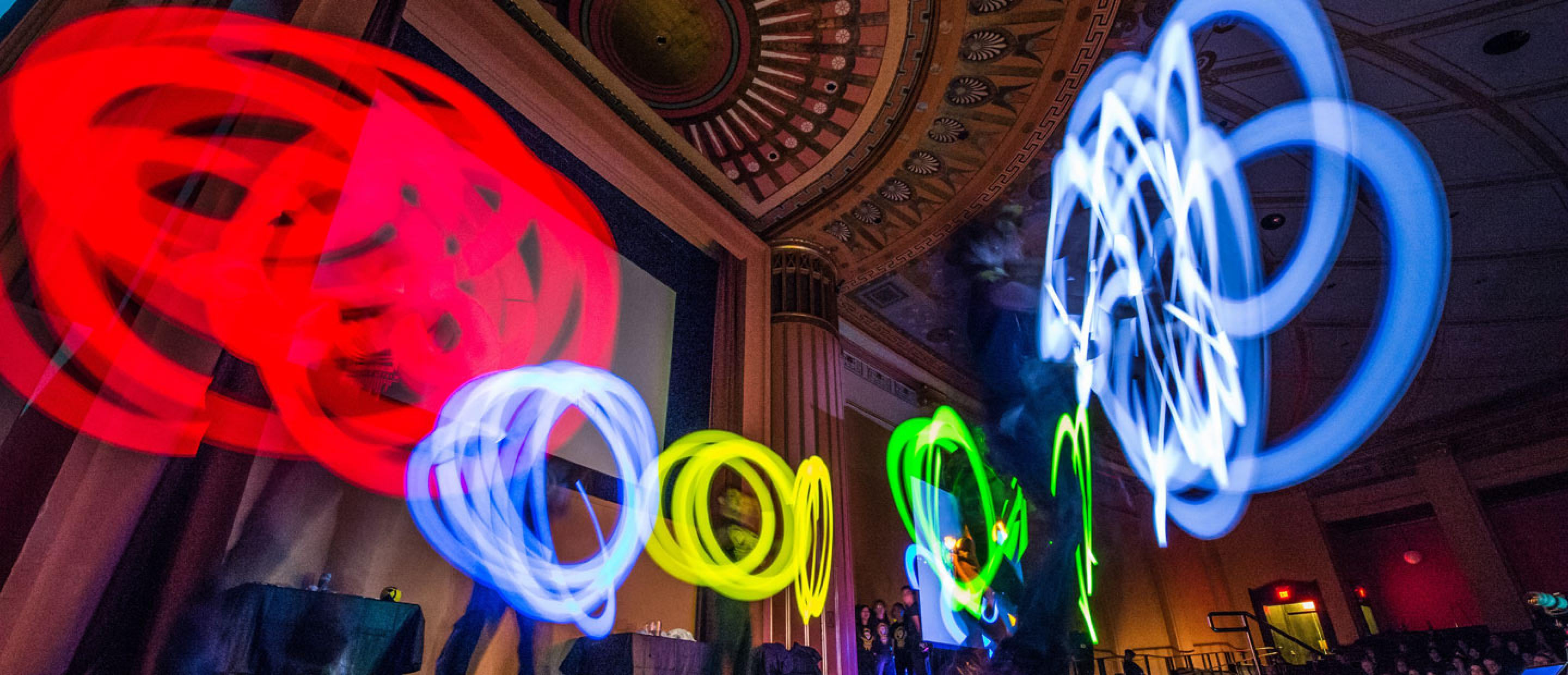 Performers spin brightly colored lights on stage at Rackham Auditorium