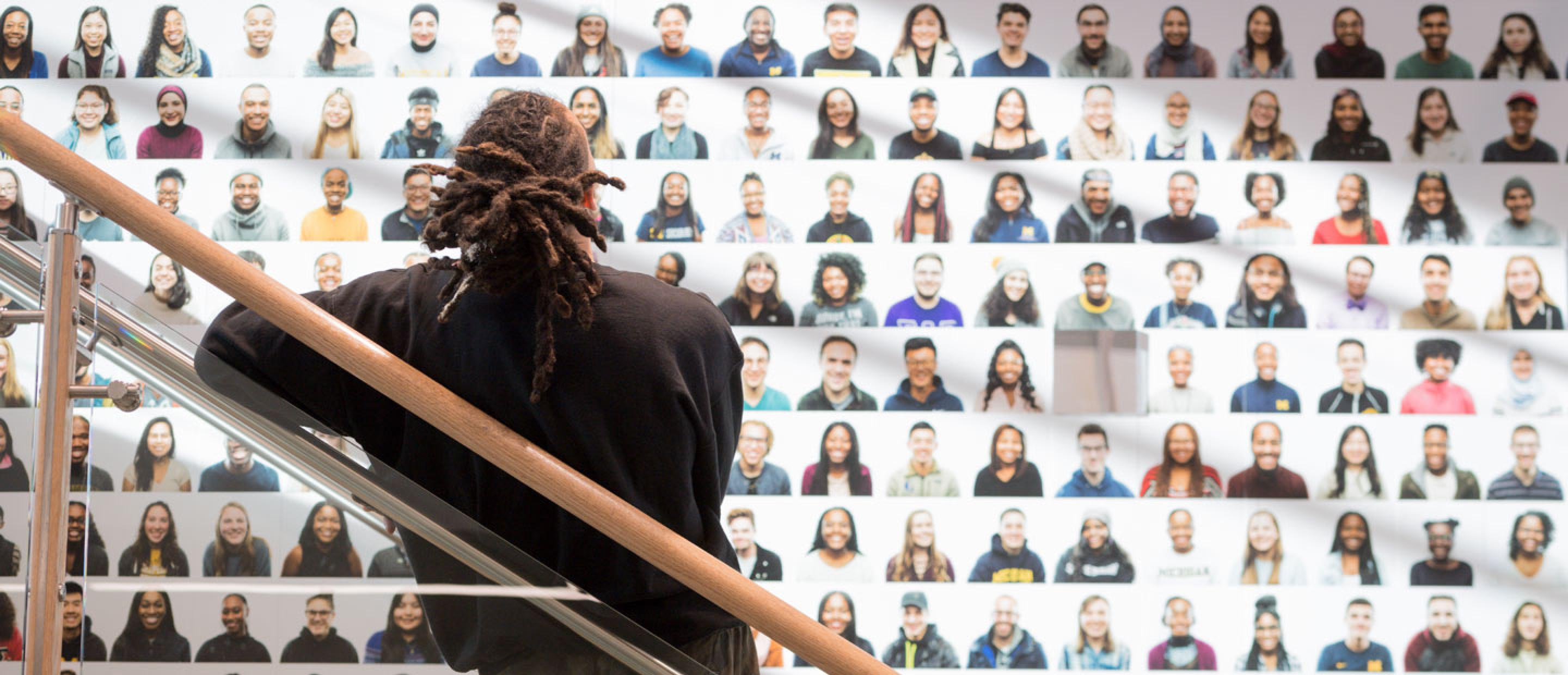 A man looks at a photo collage of the University of Michigan community