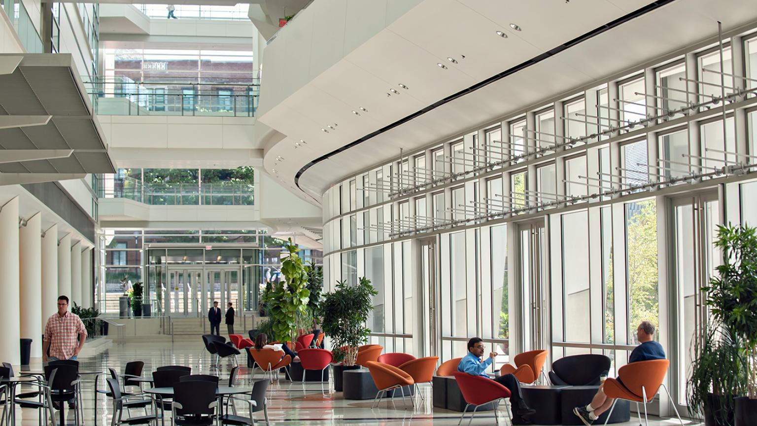 Lobby of Biomedical Sciences Research Building two researchers are sitting and talking in the sun filled lobby