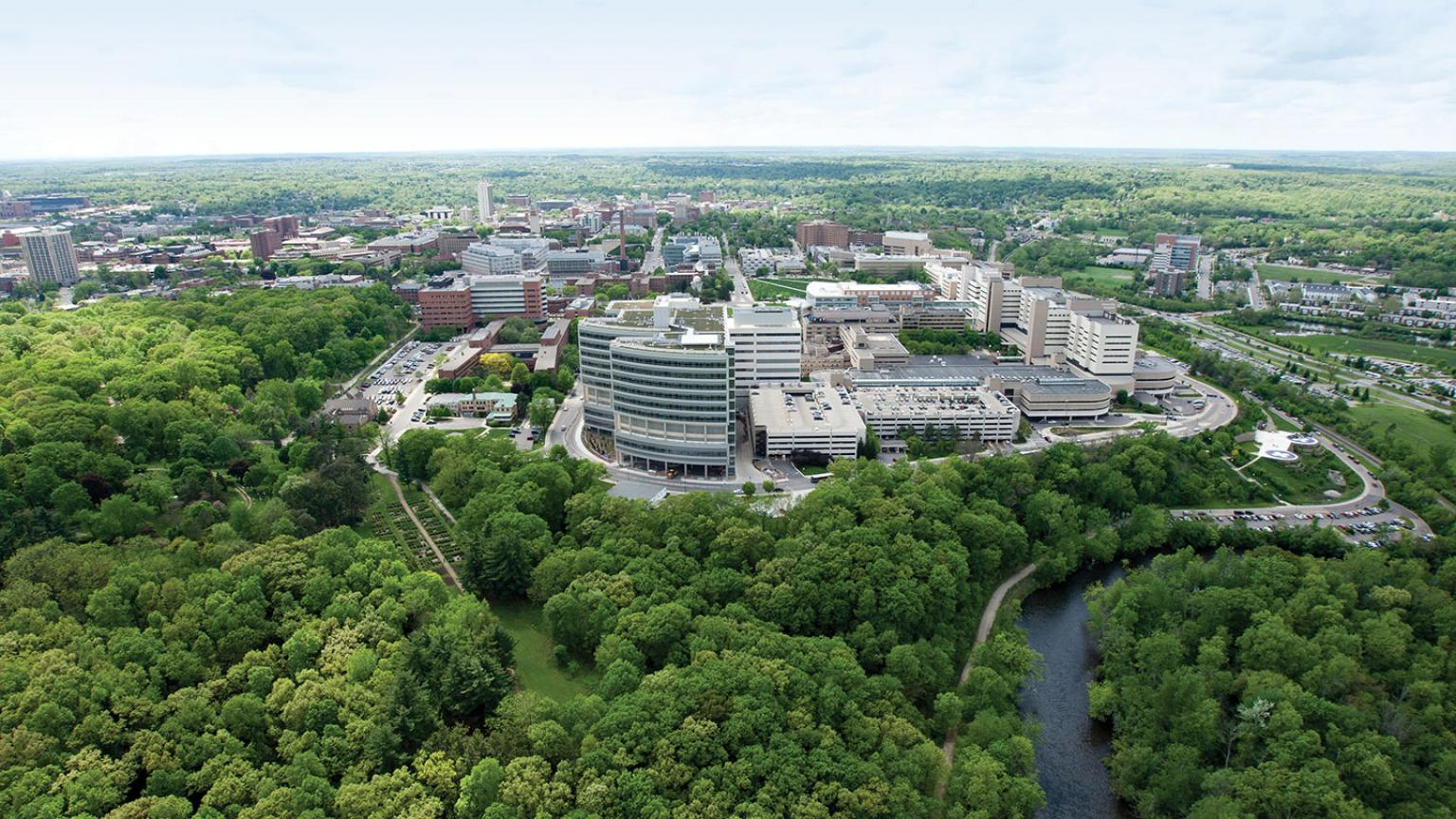 Aerial shot of Children's and Women's hospital buildings with green trees and Huron River in the foreground