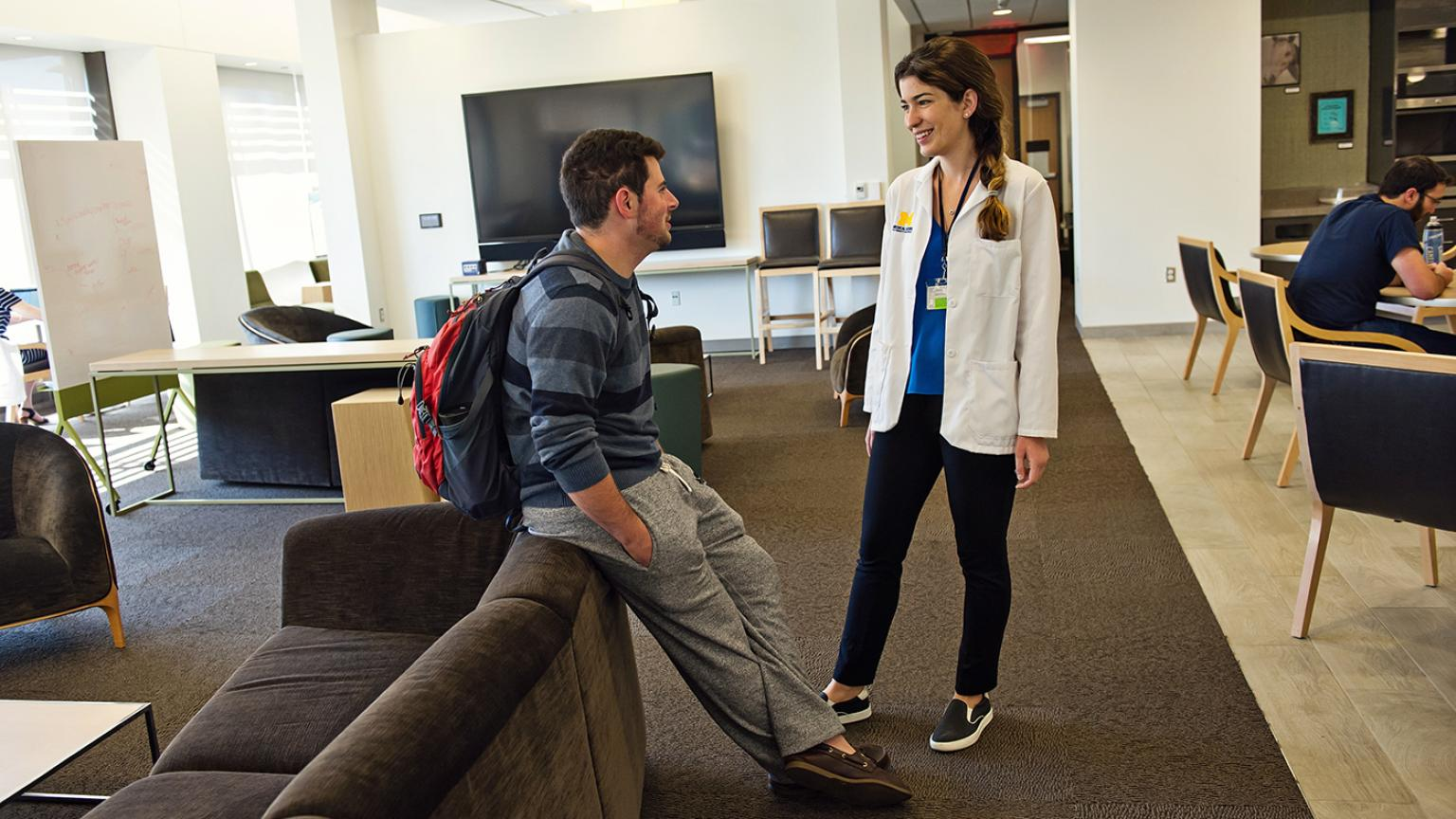 Two medical students having a conversation in the lounge, one is wearing a white coat and one is leaning against a couch