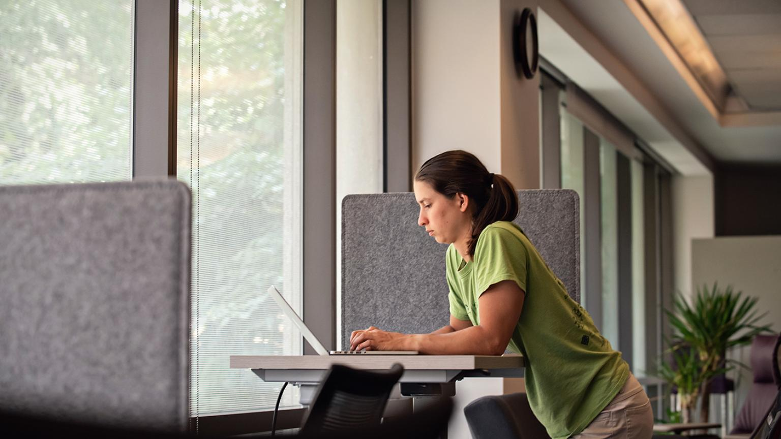 Woman working at a standing desk in front of a window in the OGPS lounge