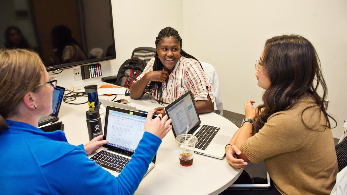 Students studying together in small meeting room