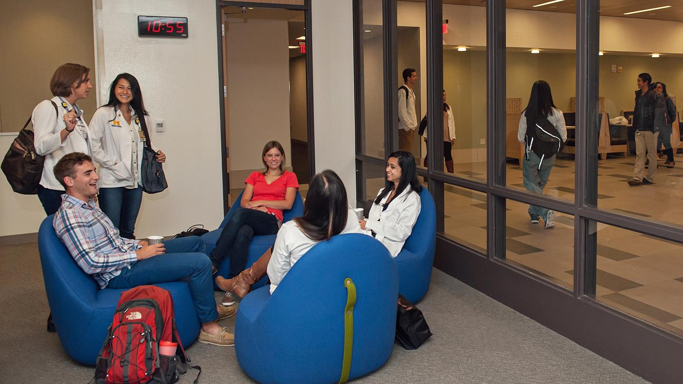 Four students are sitting in squishy chairs on the floor