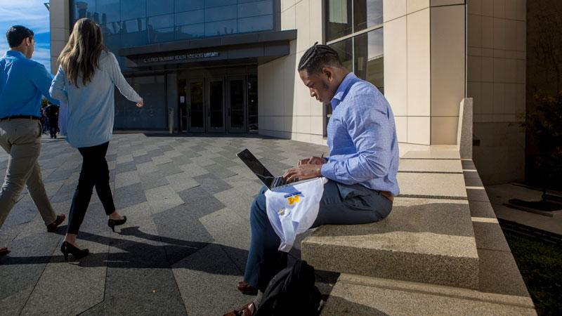 A medical student works on a laptop outside the Taubman Health Sciences Library