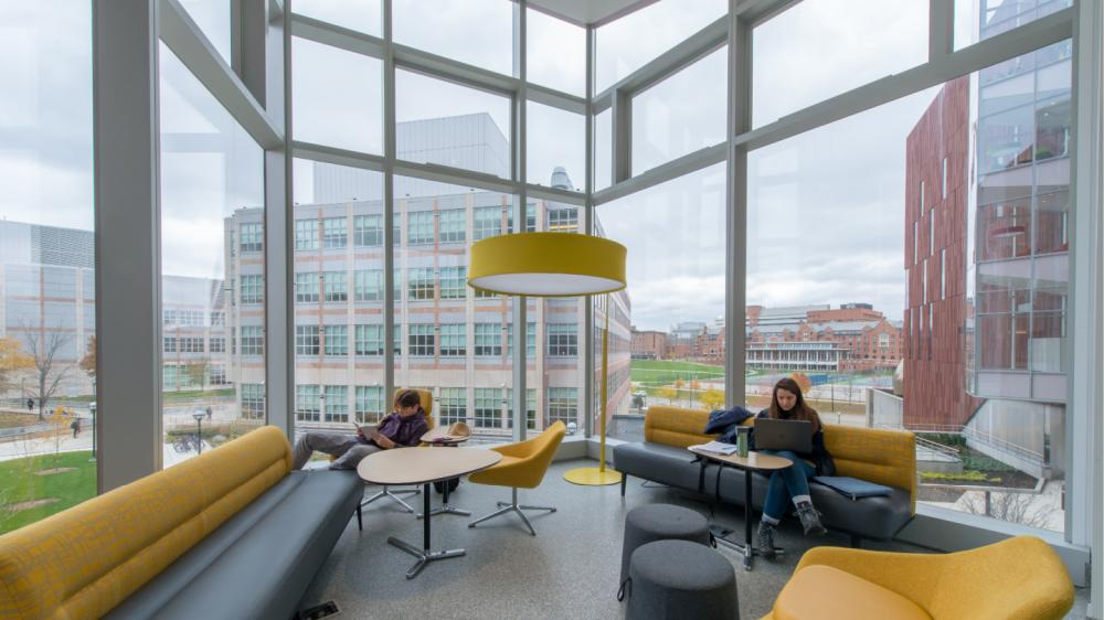 People sitting in a lounge space with views of campus