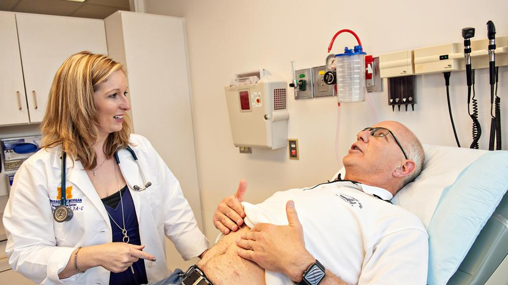 Patient room with white female MD talking to an older white male patient who is is showing his stomach