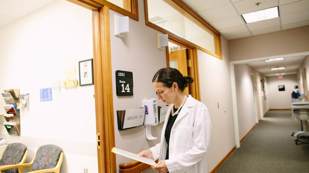 White female MD in white coat is consulting a patient file before she enters a patient exam room