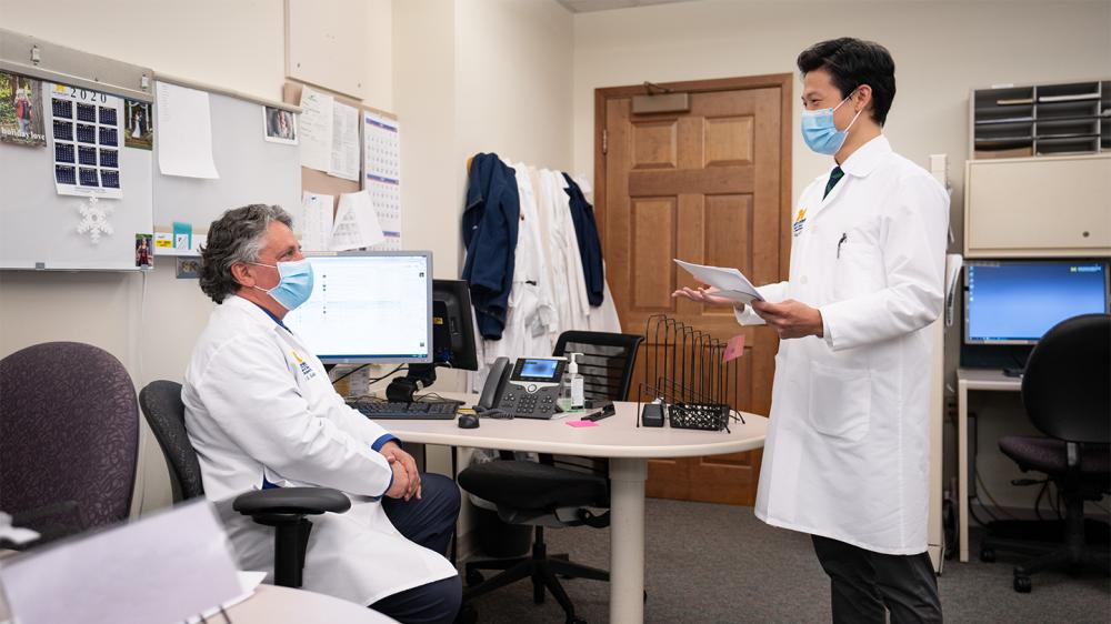 Two male MD's wearing masks are discussing a file at a computer in an office