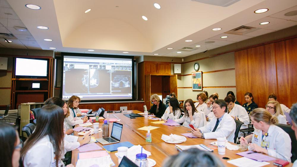 Twenty Two people sitting in a conference room at a long table discussing scans up on a large screen