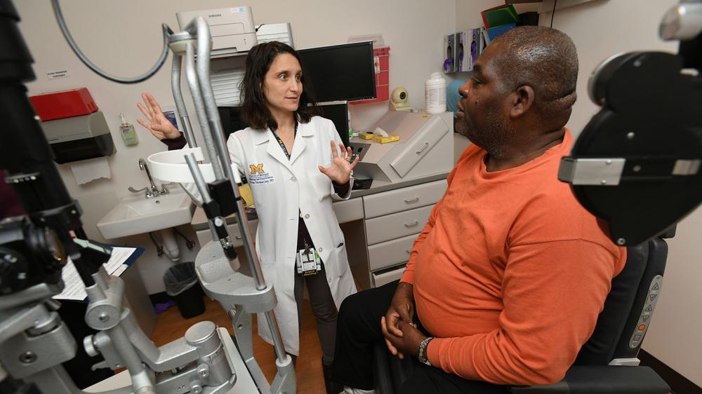 White female clinician talking with Black male patient in an exam room