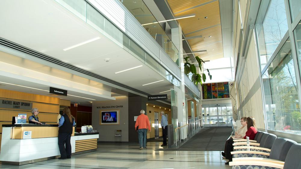 Kellogg lobby area with welcome desk, chairs lined along windowed wall, colorful artwork, and green plants