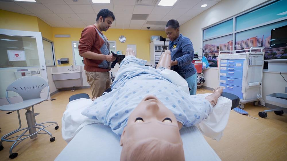Two learners are in a simulated labor room with a dummy in labor on the patient bed
