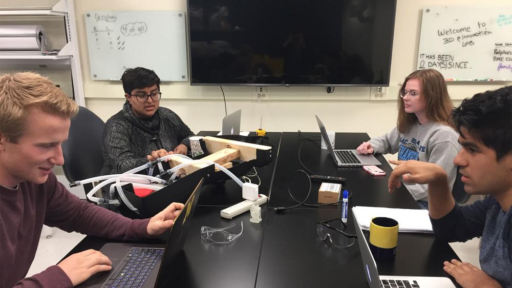 four students are working on computers at a desk together in the SC 3D & Innovations Lab