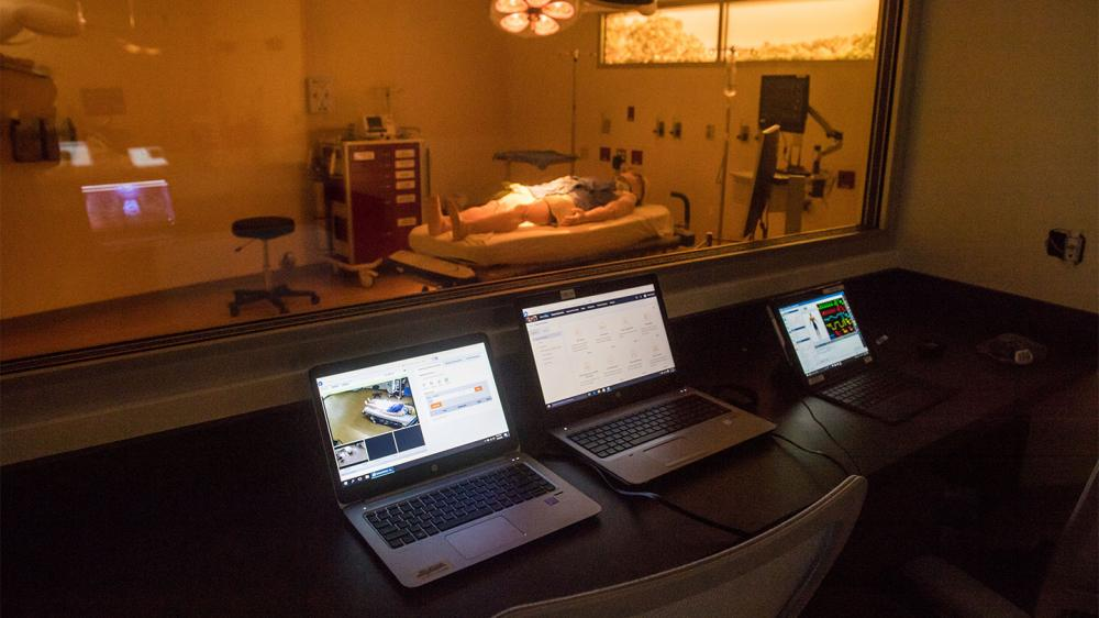 Empty control room with 3 screens and dummy patient viewable in the next room