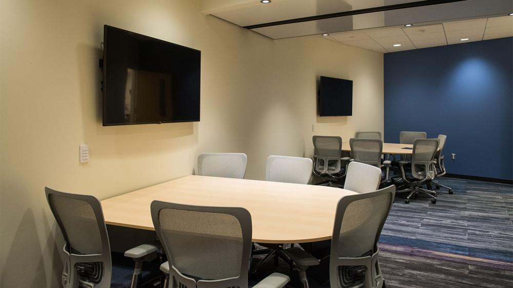 Room with two tables with chairs facing digital screens