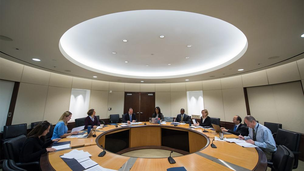 Circular conference room and circular conference table with 9 people meeting