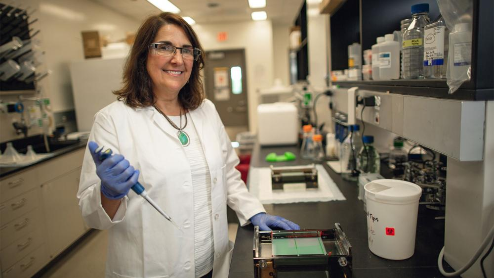 Female researcher smiling at camera wearing lab googles, gloves, and holding a pipette