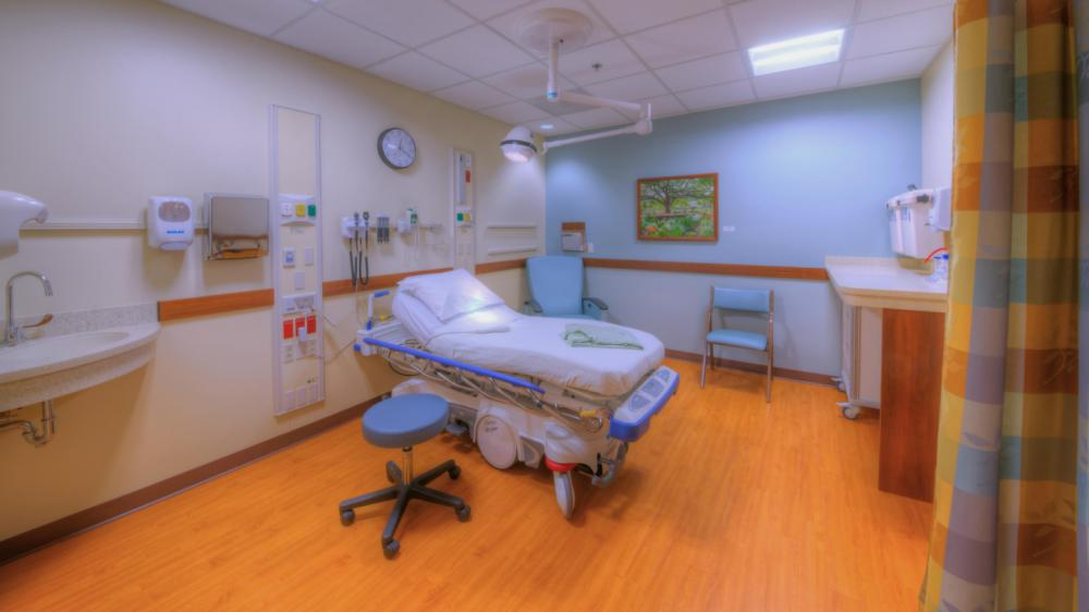Empty clinical exam room with patient bed, sink and chair