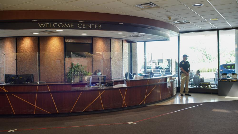 Large desk area labeled Welcome Center with plexiglass divides between greeter and visitor