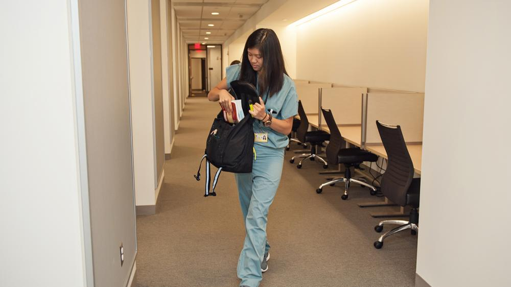 A woman in scrubs is walking out of a cubby study space putting a book in her backpack