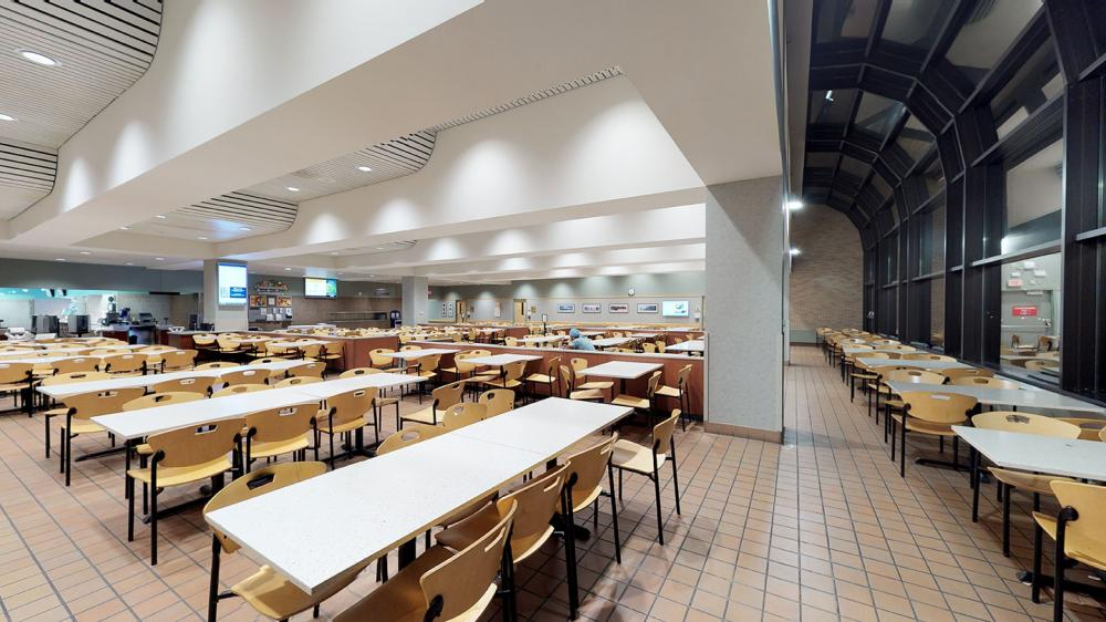 Empty cafeteria dining area with tables and chairs and floor to ceiling windowed wall
