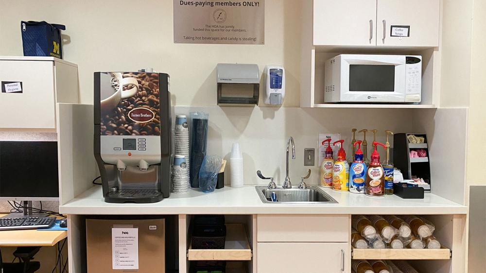 Lounge coffee station with coffee machine, cups, flavored syrups, and microwave