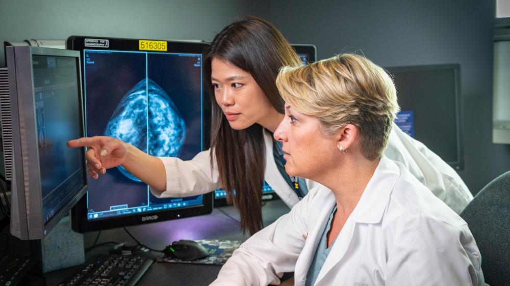 Two women are examining mammogram images on a several computer screens