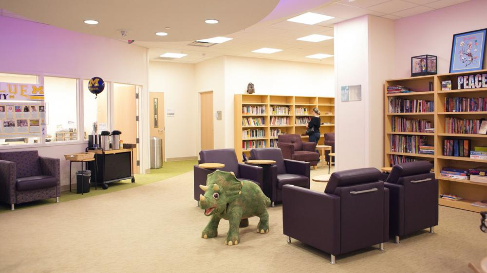 Empty Family Center with comfortable chairs, bookshelves, and large stuffed green dinosaur
