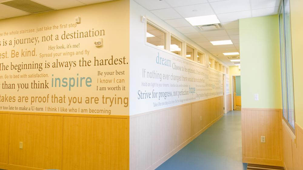 empty light filled hallway with inspirational quotes written on the wall