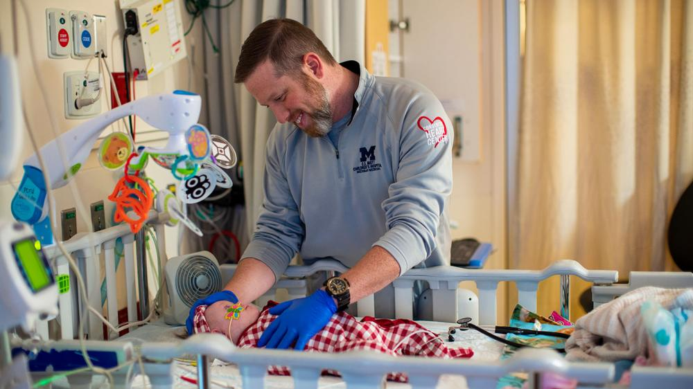 Male nurse caring for baby in a hospital crib with colorful mobile