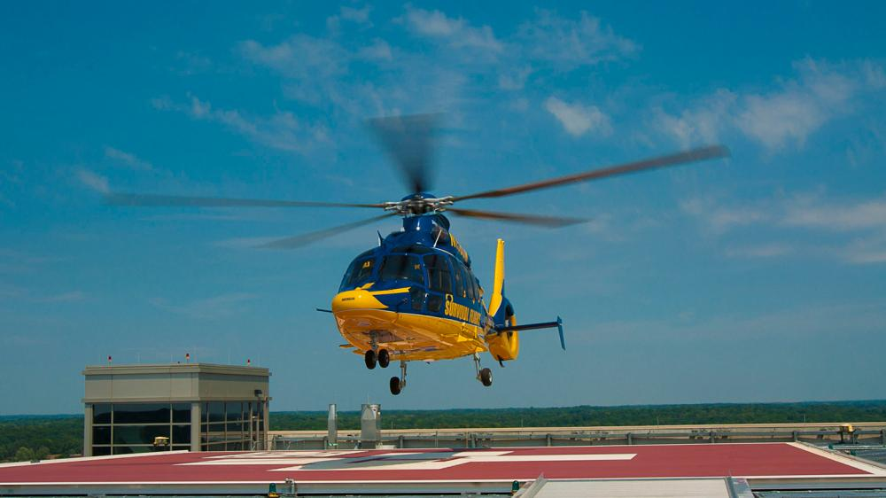 Survival Flight helicopter landing on the helipad on top of the Mott building