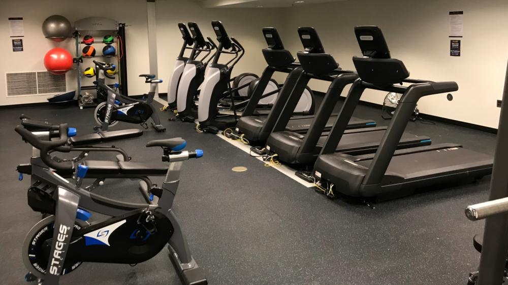 Unoccupied small fitness room with weights and cardio machines