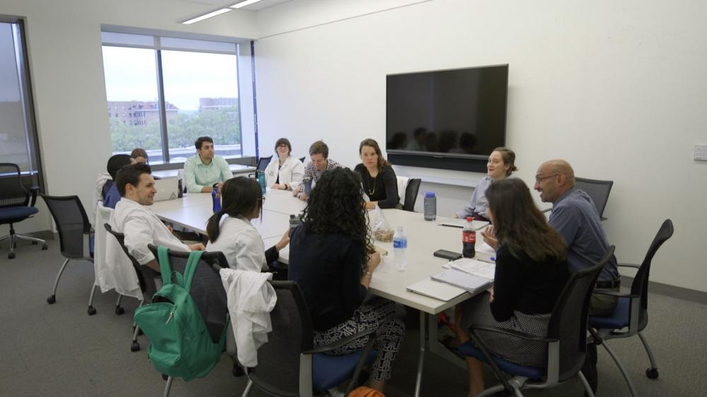Medical students and faculty gathered around large table talking