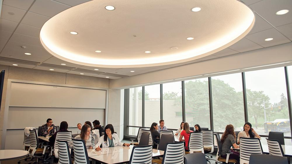 Students and professionals are collaborating around large whiteboard tables in a natural light filled room