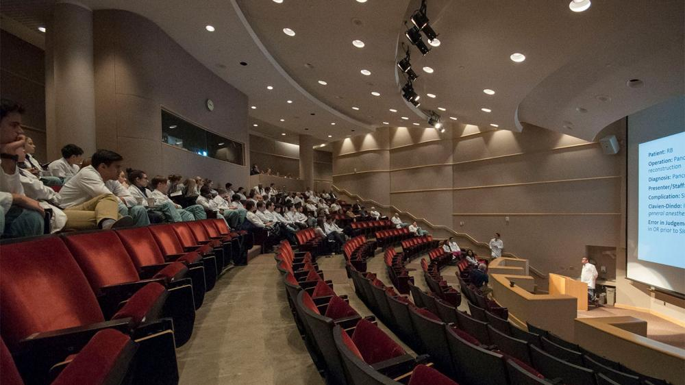 Auditorium with case study lecture happening at the front and audience members in white coats