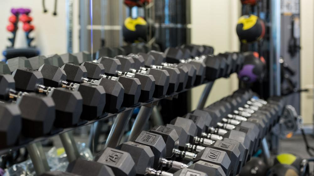 Rack of different weights of dumbells lined up against a large mirrored wall
