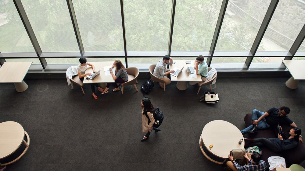 Overhead shot of groups of students working at small cafe tables next to a wall of windows