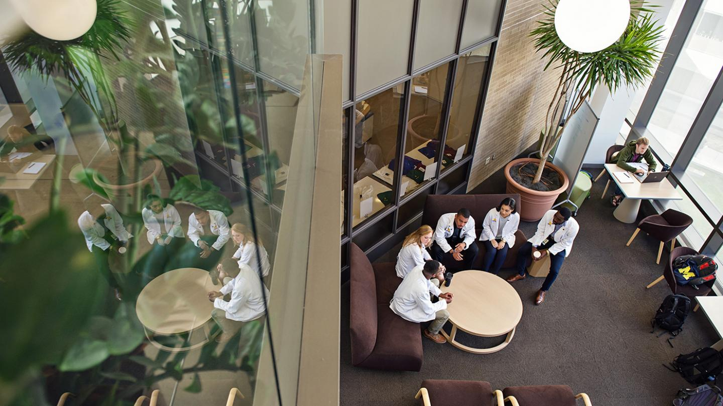 Overhead shot of five students on couches having a discussion around a round table