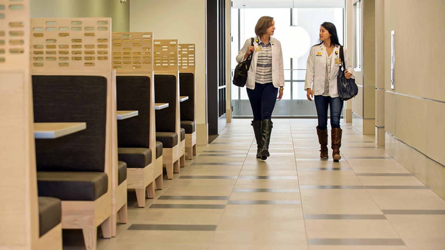 Two student are walking by several padded study booths with large center tables