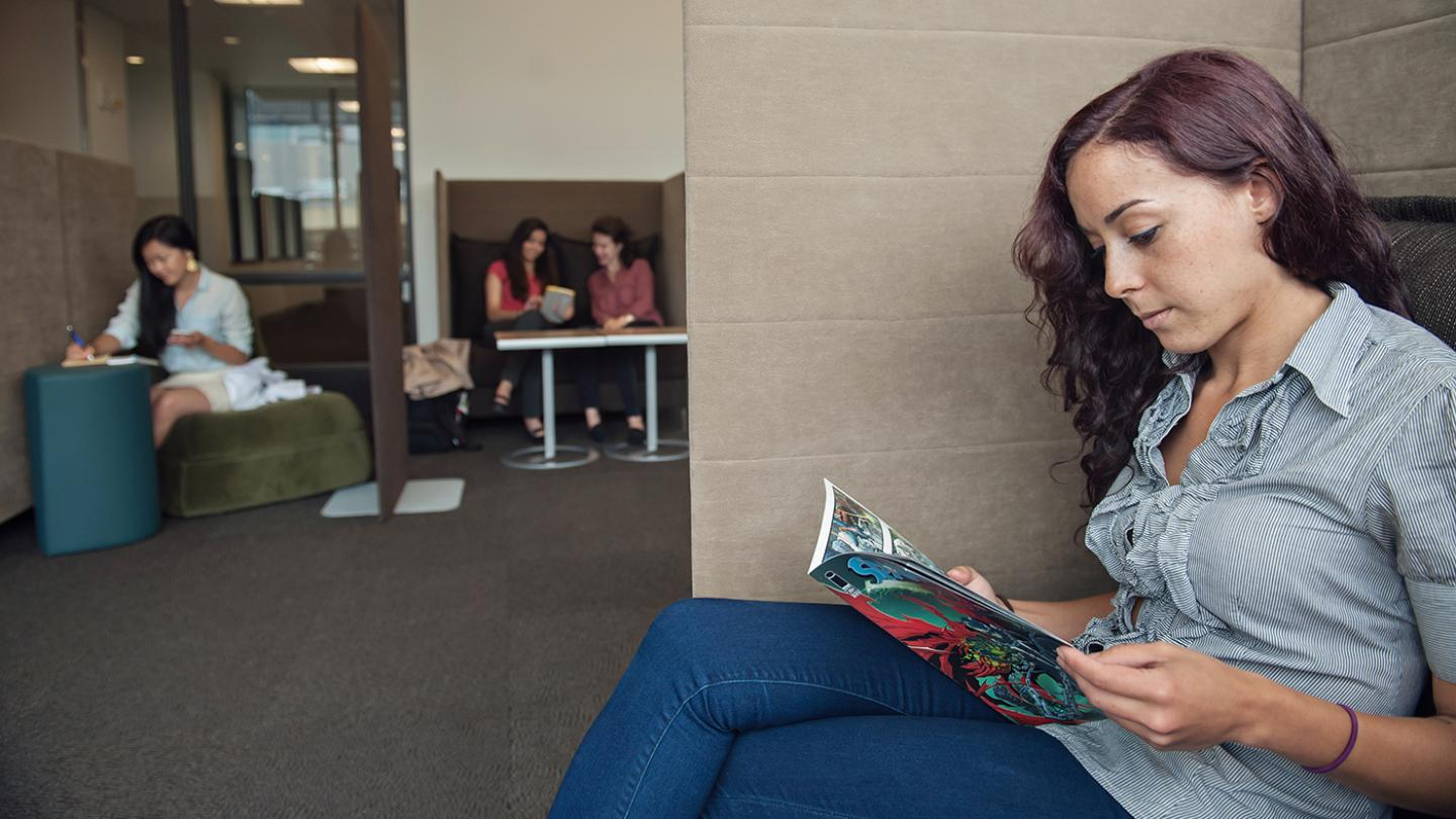 Student sitting in a quiet space reading a comic while other students behind her are working in cubicles